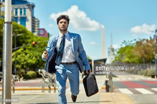worried argentine businessman rushing to appointment - approaching stock pictures, royalty-free photos & images