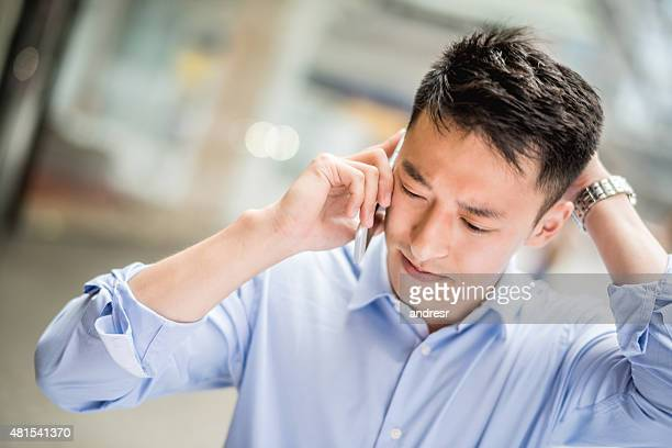 Worried Asian man talking on the phone