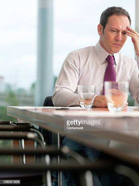 worried business man sitting at office desk - chairperson stock pictures, royalty-free photos & images