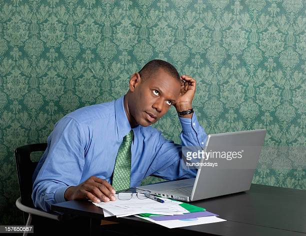 Worried business man with laptop and documents at work