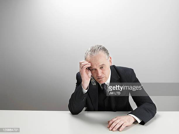 worried businessman at desk with head in hand - crisis stock pictures, royalty-free photos & images