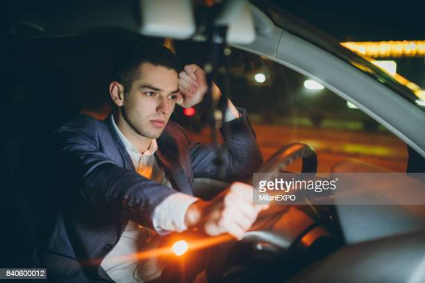 worried businessman driving car at night - transportation occupation stock pictures, royalty-free photos & images
