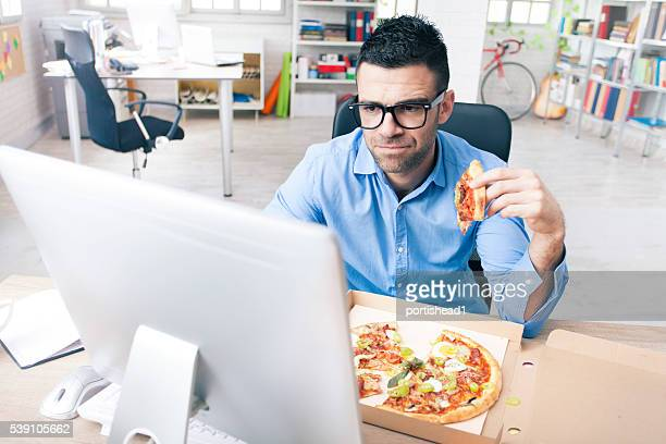 Worried businessman eating pizza at the office