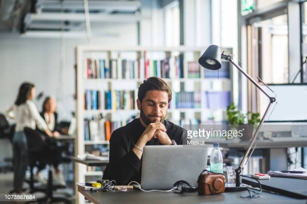 worried businessman looking at laptop while sitting in office - incidental people stock pictures, royalty-free photos & images