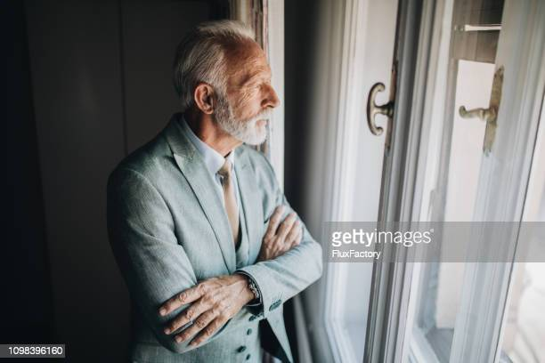 worried businessman looking through a apartment window - rich old man stock photos and pictures