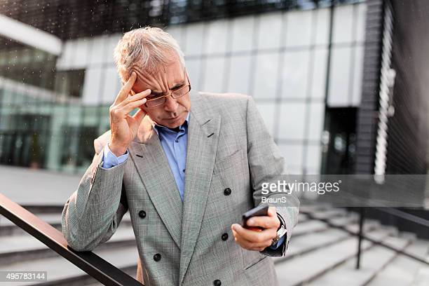 Worried businessman reading a text message on smart phone.
