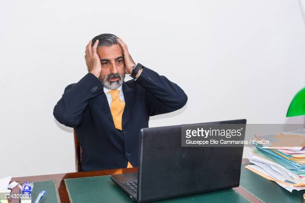 Worried Businessman With Head In Hands Using Laptop At Desk Against White Background