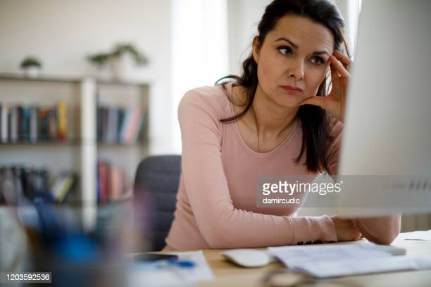 worried businesswoman looking at computer screen - frustration stock pictures, royalty-free photos & images