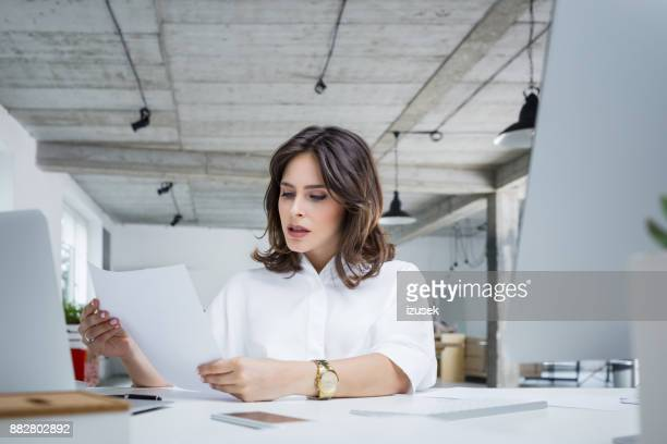 worried businesswoman reading a document - formal stock pictures, royalty-free photos & images