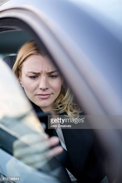 Worried businesswoman reading texts on smartphone in city traffic jam
