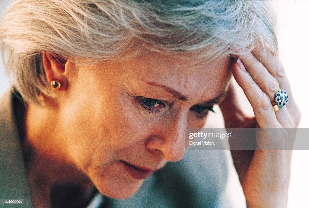 Worried businesswoman resting head in hand : Stock Photo