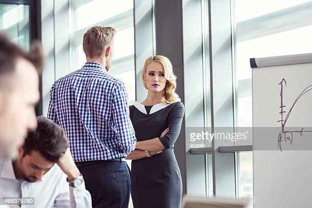 Worried businesswoman talking with her colleague in meeting room