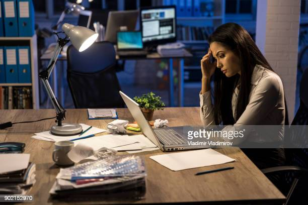 Worried businesswoman working at night
