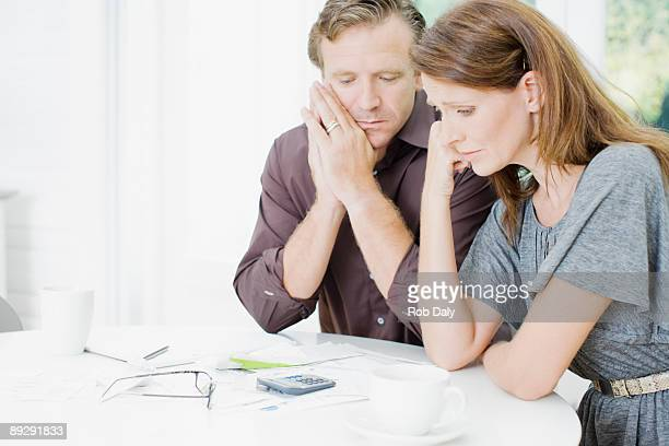 Worried couple at table paying bills