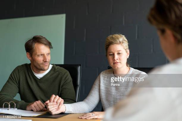 worried couple holding hands at doctor's office - mid adult men stock pictures, royalty-free photos & images