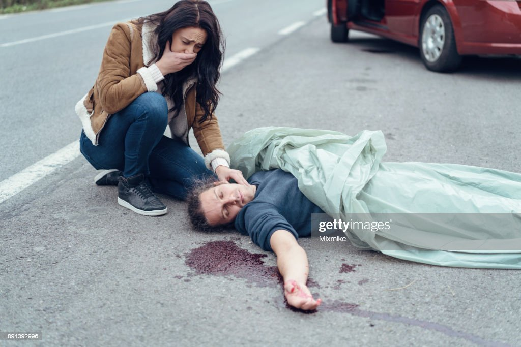 Worried crying woman checking the pulse of injured man : Stock Photo