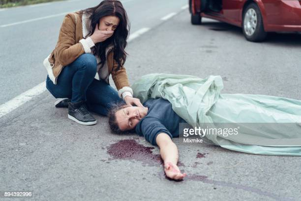 Worried crying woman checking the pulse of injured man