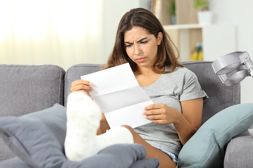 Worried disabled woman reading a letter 1010556388