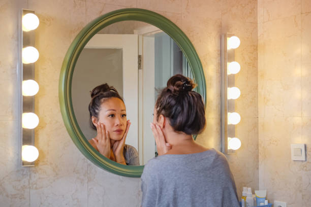 worried east asian woman checking her face skin in the mirror. - women stock pictures, royalty-free photos & images