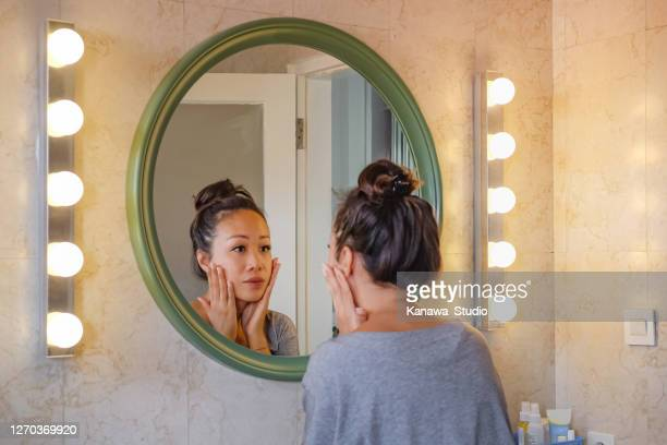 worried east asian woman checking her face skin in the mirror. - china: through the looking glass stock pictures, royalty-free photos & images