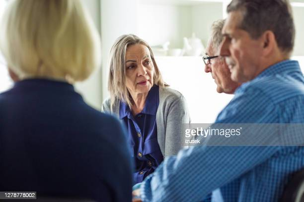 worried eldery lady during group therapy - izusek stock pictures, royalty-free photos & images