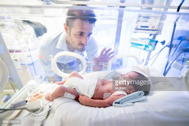 worried father at the nicu touching the incubator where is premature newborn son is - delivery room stock pictures, royalty-free photos & images