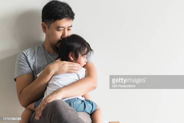 worried father comforts ill son - stay at home father stock pictures, royalty-free photos & images