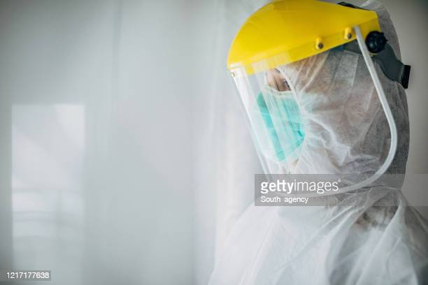 worried female doctor in full protective suit in the hospital - helmet visor stock pictures, royalty-free photos & images