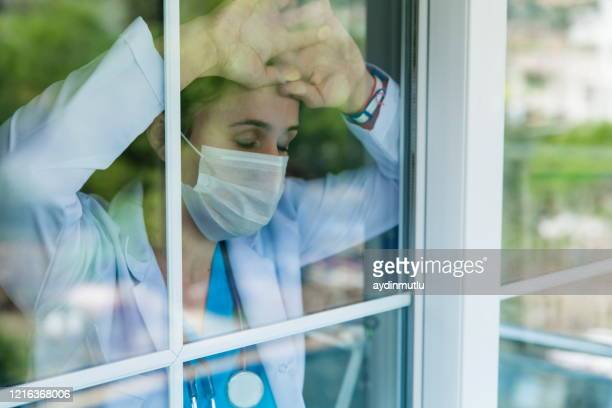 worried female doctor looking through the hospital window - stress coronavirus stock pictures, royalty-free photos & images