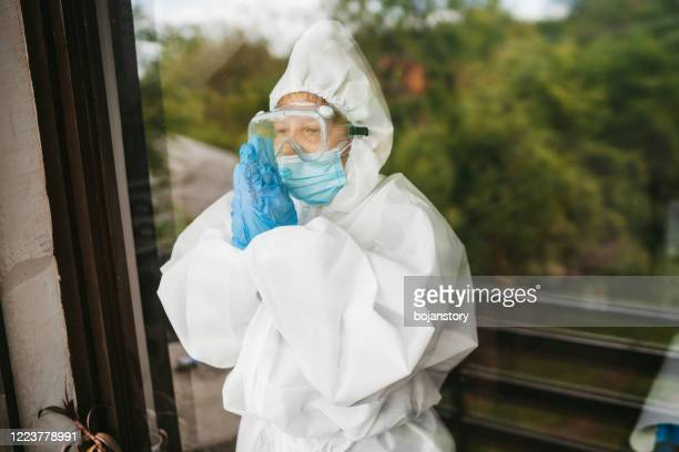 worried female doctor praying on hospital window - frontline worker stock pictures, royalty-free photos & images