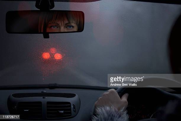 worried female motorist on a lonely road at night - rear view mirror stock pictures, royalty-free photos & images