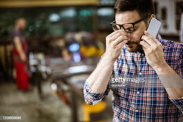 worried foreman talking on cell phone in a workshop. - burden stock pictures, royalty-free photos & images