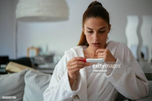 fille inquiet après avoir regardé un test de grossesse - test de grossesse photos et images de collection