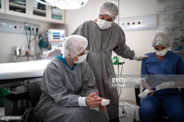 worried healthcare coworkers at operating room in hospital - stress coronavirus stock pictures, royalty-free photos & images