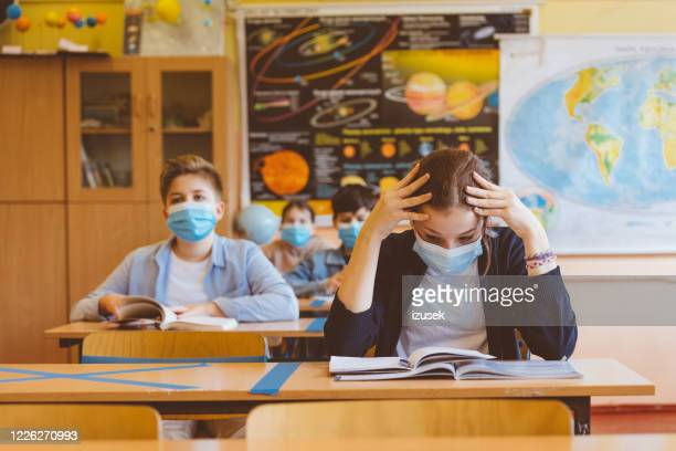 worried high school girl student at school wearing n95 face masks - school building stock pictures, royalty-free photos & images
