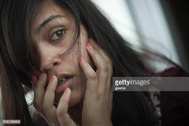 Miedo de mujer joven India poner su mano en la boca.