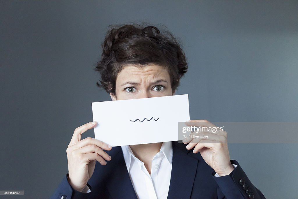 A worried looking woman holding paper with squiggle sign : ストックフォト