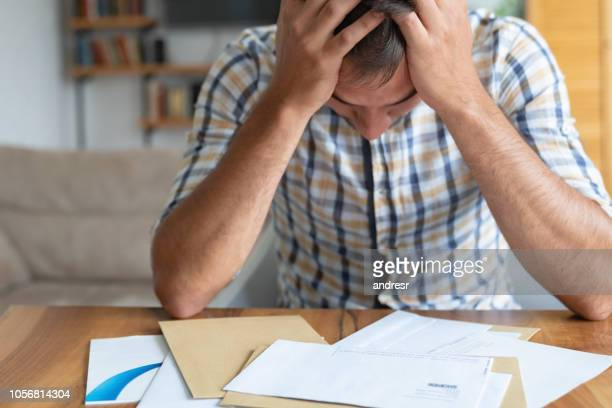 Worried man at home checking his mail