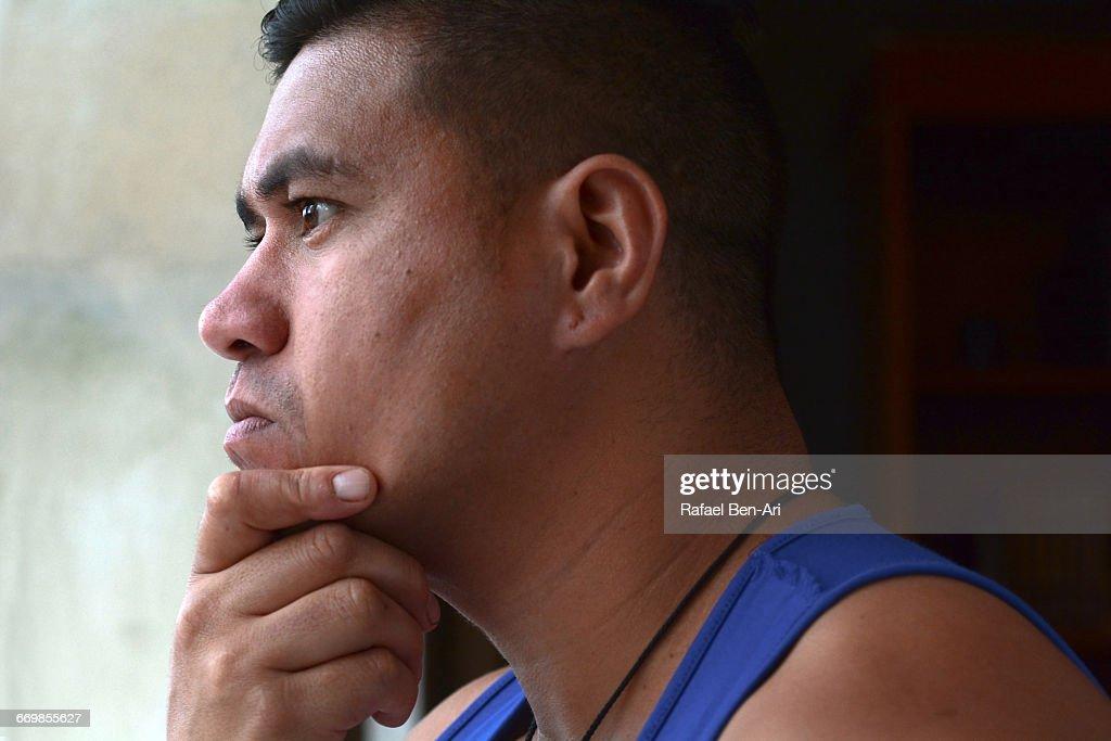Worried Man Looks outside a window : Stock Photo