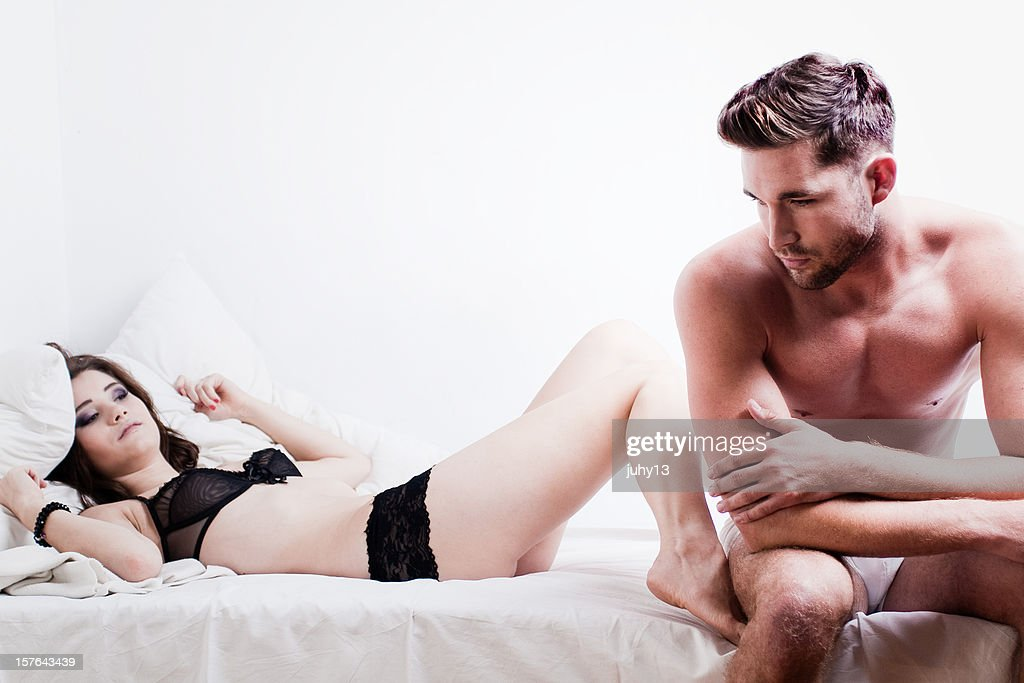Worried man on edge of bed with impatient female partner : Stock Photo