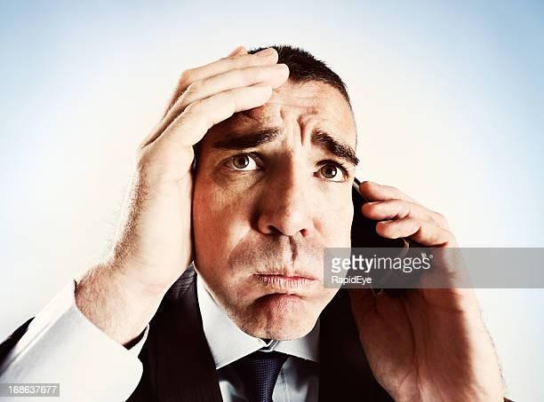 Besorgt Mann auf Handy grimaces, der seinen Kopf kratzen