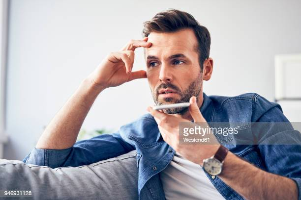 worried man sitting on sofa using cell phone - banging your head against a wall stock pictures, royalty-free photos & images