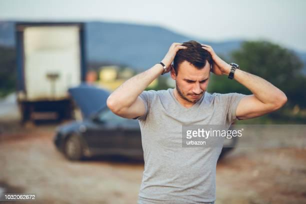 壊れた車の横に立っている心配人