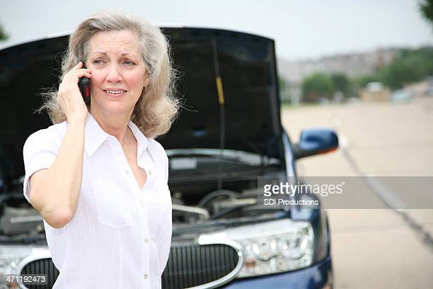 Worried Mature Adult Calling for Help With Her Car
