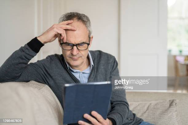 worried mature caucasian man looking at tablet device - candid forum stock pictures, royalty-free photos & images