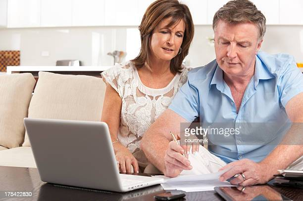 Worried mature couple doing paperwork