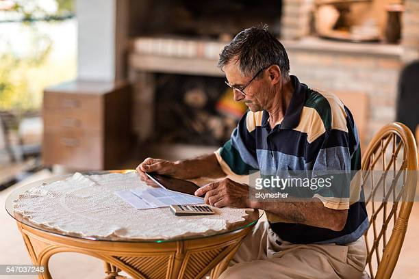 Worried mature man going through home finances on touchpad.