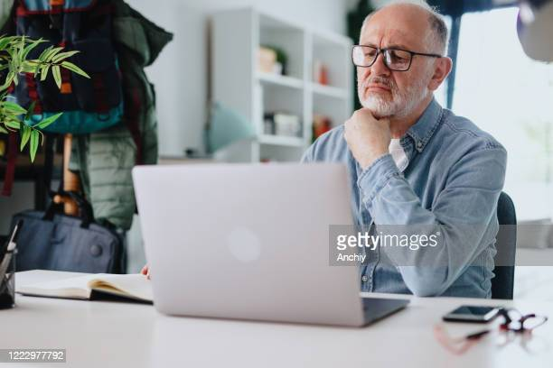 worried mature man in front of a laptop at home - avoidance stock pictures, royalty-free photos & images