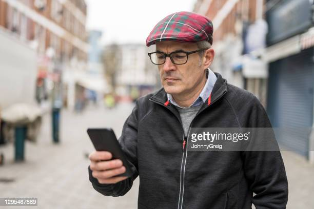 worried mature man looking at his smart phone outdoors - candid forum stock pictures, royalty-free photos & images