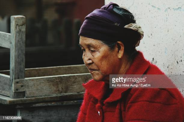 worried mature woman sitting outdoors - ko ko htike aung stock pictures, royalty-free photos & images